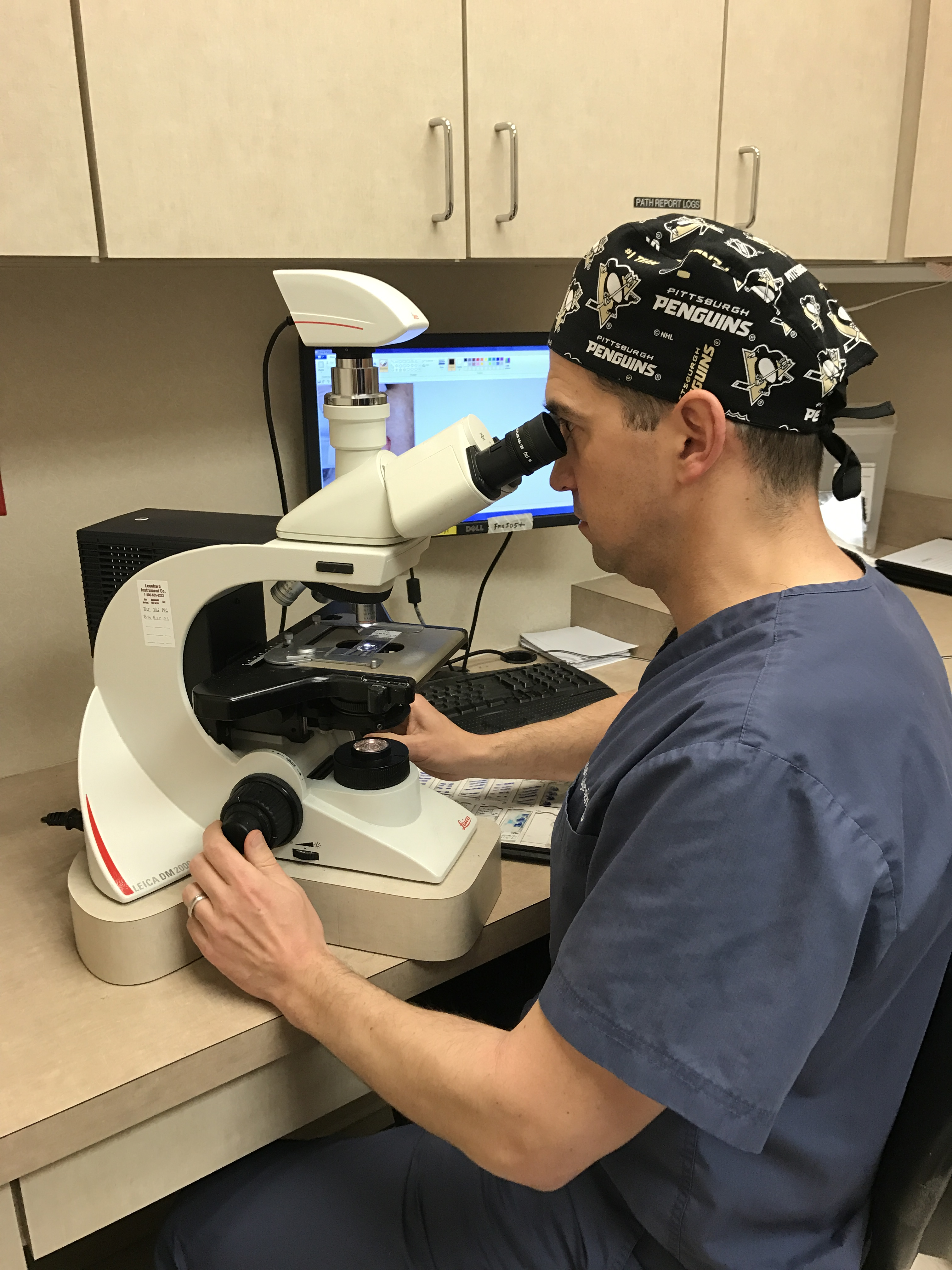 Dr. Justin Vujevich examining tissue at the microscope.